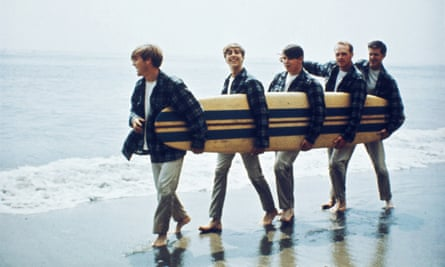 Beach Boys On The Beach With A Surfboard LOS ANGELES - AUGUST 1962: Rock and roll band The Beach Boys walk along the beach holding a surfboard for a portrait session in August 1962 in Los Angeles, California. (L-R) Dennis Wilson, David Marks, Mike Love, Carl Wilson, Brian Wilson