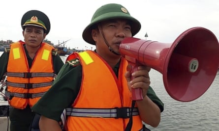 A coastguard officer speaks on a megaphone at a fishing boat shelter in Quang Binh province, Vietnam
