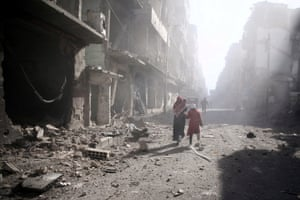 People walk past a damaged site after an airstrike in the besieged rebel-held town of Douma on the outskirts of the Syrian capital, Damascus.