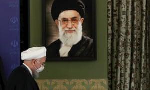Iranian president Hassan Rouhani in front of a portrait of Iran's supreme leader, Ayatollah Ali Khamenei.