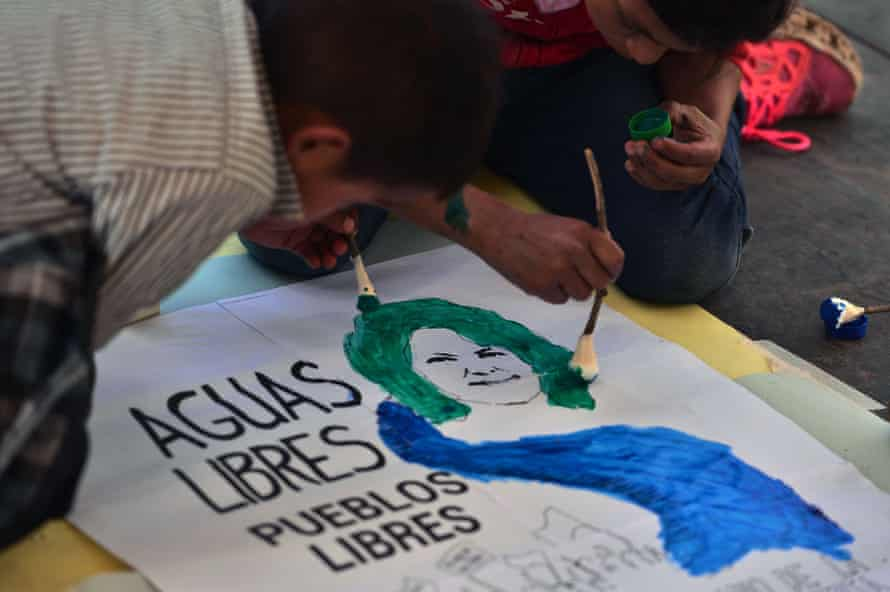 Children paint a sign during a ceremony to commemorate the fourth anniversary of the murder of environmental activist Berta Cáceres, in La Esperanza, on March 2, 2020.