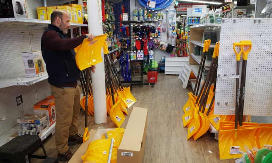 A worker in a hardware store assembles snow shovels ahead of the expected blizzard.