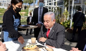 A waitress serves Israeli PM Benjamin Netanyahu as he sits in a cafe in Jerusalem where restrictions are being eased.