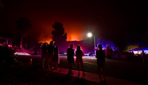People watch as the Bobcat Fire burns on hillsides behind homes in Arcadia, California on Sunday.