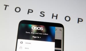 Asos seen on a smartphone with the Topshop logo behind