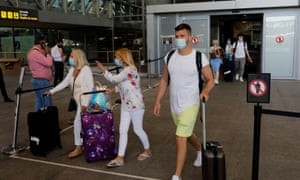 Tourists wearing protective face masks walk with their luggage as they arrive at Malaga-Costa del Sol Airport, in Malaga, Spain, 7 June.