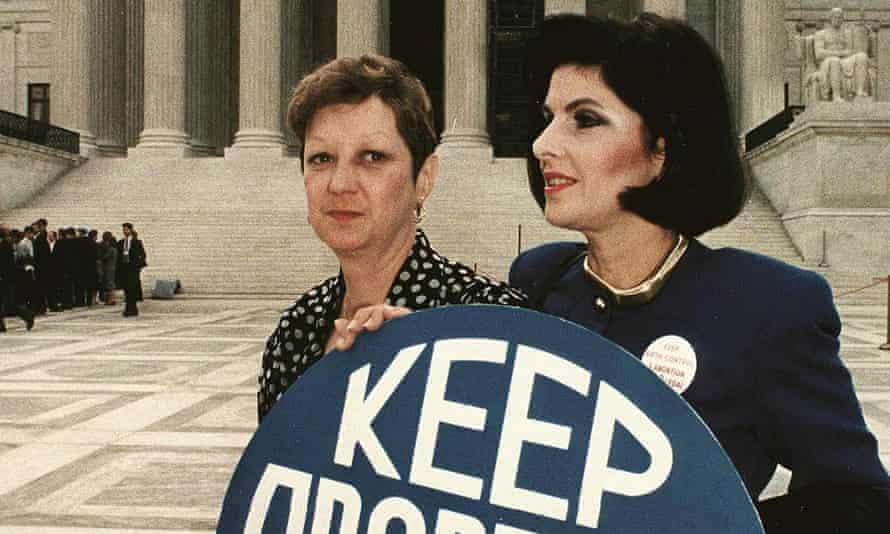 Norma McCorvey and Gloria Allred hold a sign saying 'keep abortion legal' in front of the US Supreme Court