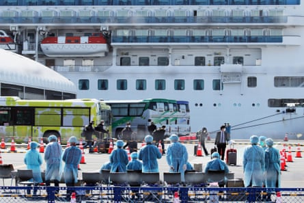 Workers in protective gear prepare to check passengers after they disembarked the Diamond Princess cruise ship at the Daikoku Pier Cruise Terminal in Yokohama, Japan, 21 February 2020.