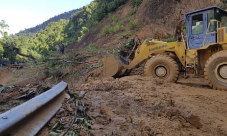 A bulldozer clears out the road damaged by landslide to access a village swamped by another landslide in Quang Nam province, Vietnam