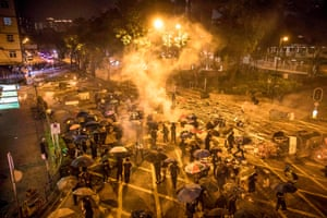 Protesters react as police fire tear gas while they attempt to march towards Hong Kong Polytechnic University in Hung Hom district