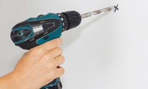 Builder or worker drilling with a machine or drill.