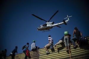 Central American migrants climb the border fence near El Chaparral border crossing in Tijuana