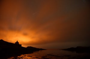 <strong>Northumberland, UK</strong> A shooting star seen through thin cloud in the skies over the Bathing House, as the annual Perseid meteor shower peaked