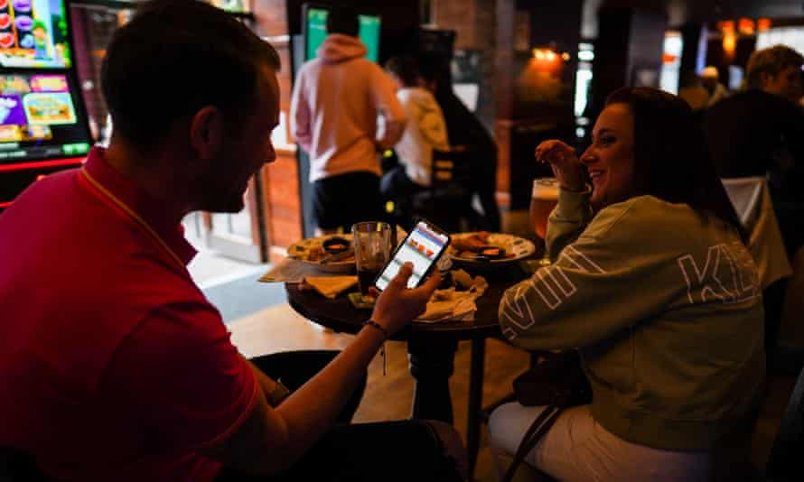 two people outside a pub, one with a smartphone