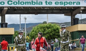 A Venezuelan woman is helped by Colombian soldiers crossing the Simon Bolivar international bridge from San Antonio del Tachira, Venezuela on 25 July 2017.