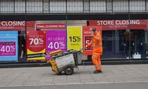 Signs in the window of a closing Debenhams store offer sales bargains on the High Street in Winchester.