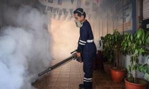 A pest control worker fumigates a school in Kuala Lumpur