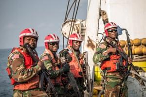 Four Liberian coastguards watch fishermen on Oriental Kim haul in nets