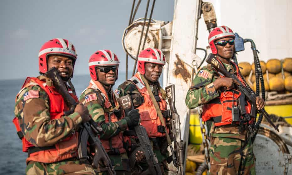 Members of Liberia's coastguard board a ship suspected of fishing illegally in the country's waters