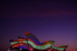 The sails of the Sydney Opera House are lit up at dawn with an artwork titled Angwirri by Indigenous artist and Yaegl woman Frances Belle-Parker.