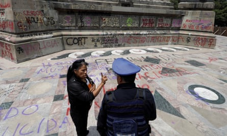 A woman speaks with a police officer near the Angel of Independence monument in Mexico City