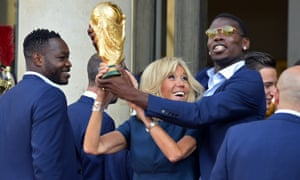 The French first lady, Brigitte Macron, holds up the World Cup trophy with Paul Pogba, at the Élysée Palace in Paris.