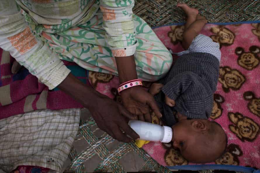 Saeeda feeds her baby daughter