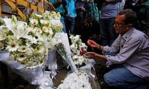 A man lights a candle at a makeshift memorial, to pay tribute to the victims of the attack on the Holey Artisan Bakery in Dhaka, Bangladesh.
