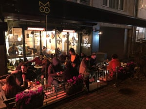 People sitting at tables outside FatCat, Istanbul, at night