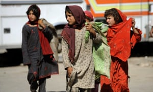 Pakistani girls walk with sacks filled with scavenged garbage in Islamabad