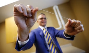 Wayne Aldredge, president of the American Academy of Periodontology, holds a piece of dental floss.