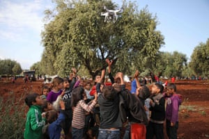 Displaced Syrian children play with a drone near a camp for displaced people in the village of Atme.