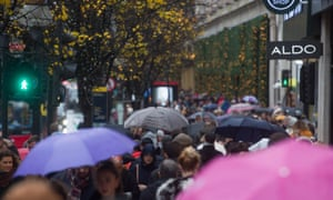 People shopping on Oxford Street in London during wet weather.