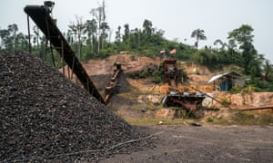 A conveyor belt feeding a pile of ore comes out of cleared jungle