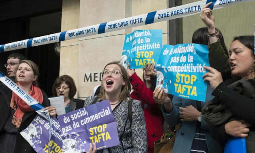 """Members of the """"Stop TAFTA"""" collective stand outside the building of French employers' organisation after being removed for interrupting the Transatlantic Trade and Investment Partnership (TTIP) conference in Paris."""