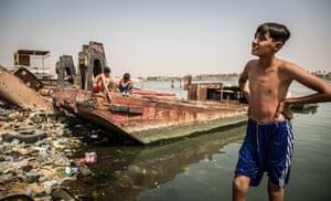Children playing on the rubbish-strewn shore of the Shatt al-Arab