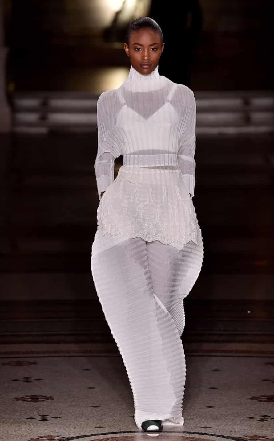A model wears a conical bra under sheer, darted knitwear.
