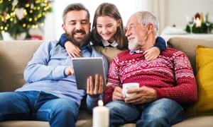 A happy small girl and her father and grandfather sitting on a sofa at Christmas time, using tablet