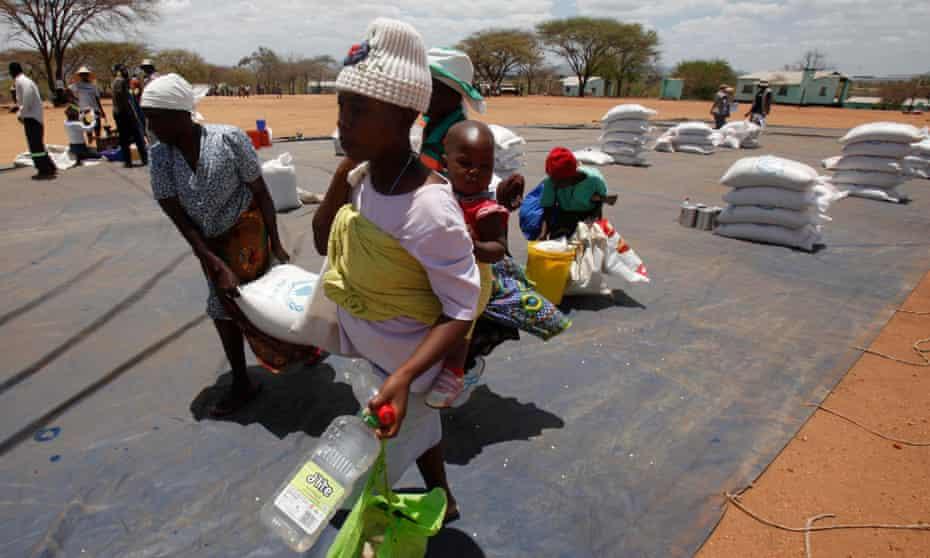 Zimbabweans collect grain distributed by World Food Programme (WFP) on November 25, 2013 in East Mashonaland, Zimbabwe.