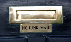 A sign saying No Junk Mail under the letterbox of a front door of a house