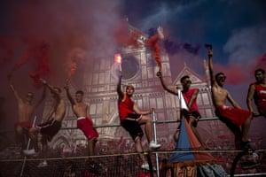 Supporters of the Santa Maria Novella Rossi team light flares before the match of the Calcio Storico Fiorentino at Piazza Santa Croce.