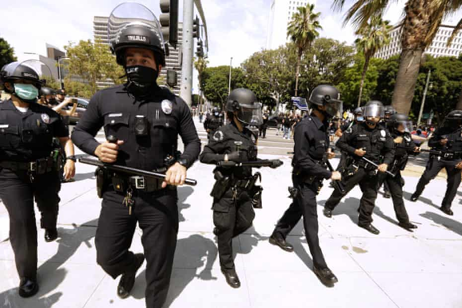 Los Angeles police officers survey a protest in downtown Los Angeles on 14 August.