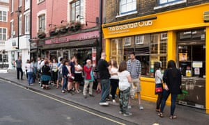 Customers queue outside the Breakfast Club cafe in Soho, London