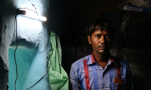 Rajesh stands beside a solar light installed in his home by a student group – one of two functioning lights in the entire village of Rajghat