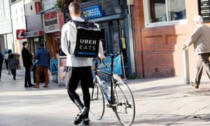 Young man walking with bicycle and UBER EATS (Ubereats) food delivery rucksack