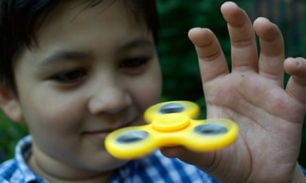 A boy plays with a fidget spinner.