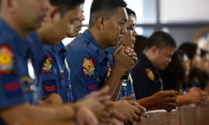 Filipino police pray during a mass held to support Duterte's anti-drugs campaign.