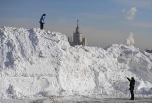Moscow, Russia: A police officer talks to a woman walking on a pile of snow cleared from Red Square