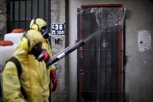A women watches residents disinfect the streets in the Villa 31 neighbourhood of Buenos Aires.