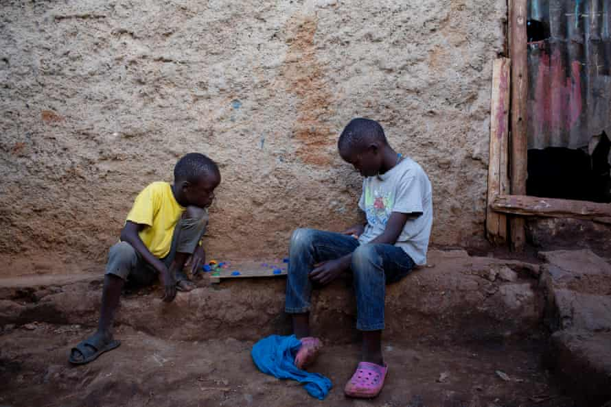 Two boys play a board game in front of their homes